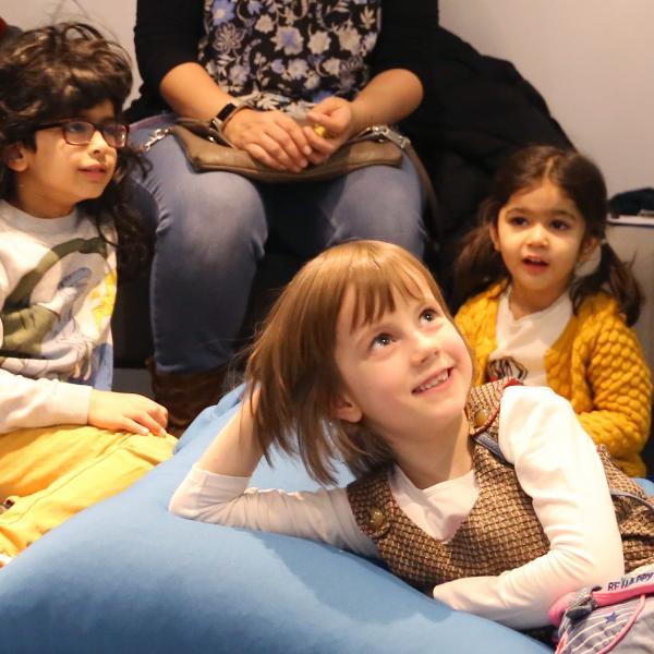 Three children listen to a performance