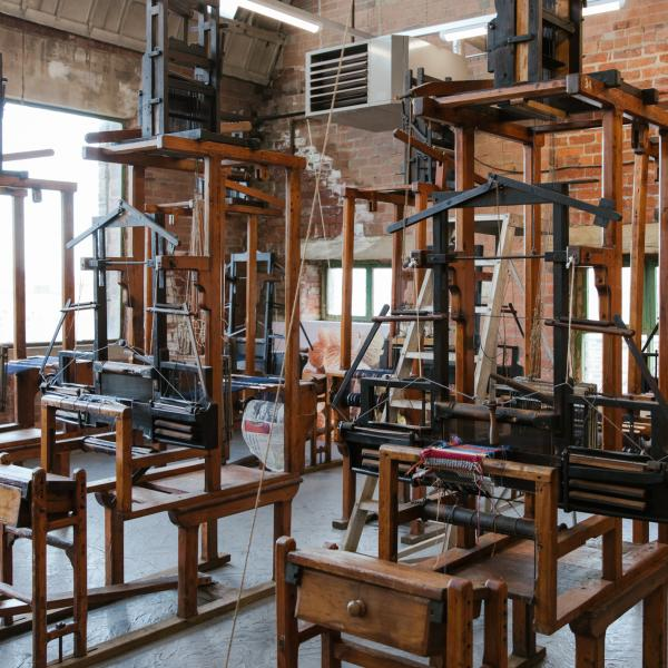 six brown wooden textile looms in a room with brick walls