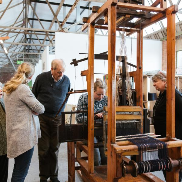 a group of people gathered around a teacher weaving on a loom