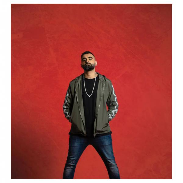 Comedian Tez Ilyas pictured wearing a jacket and chain