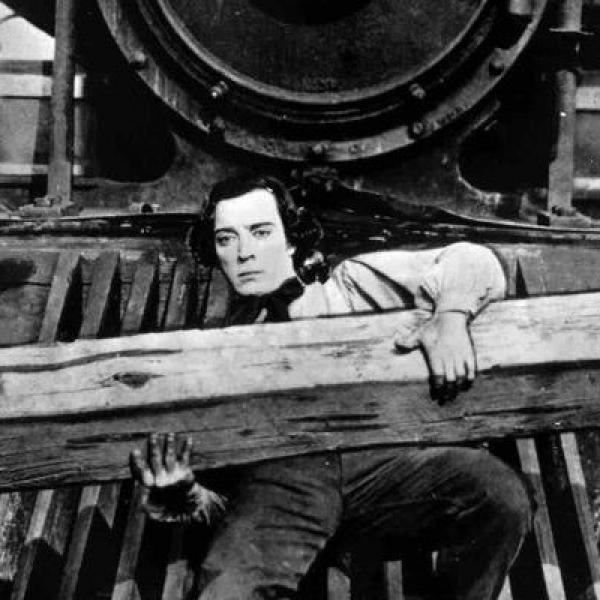 A man stands in front of a train holding a wooden plank.