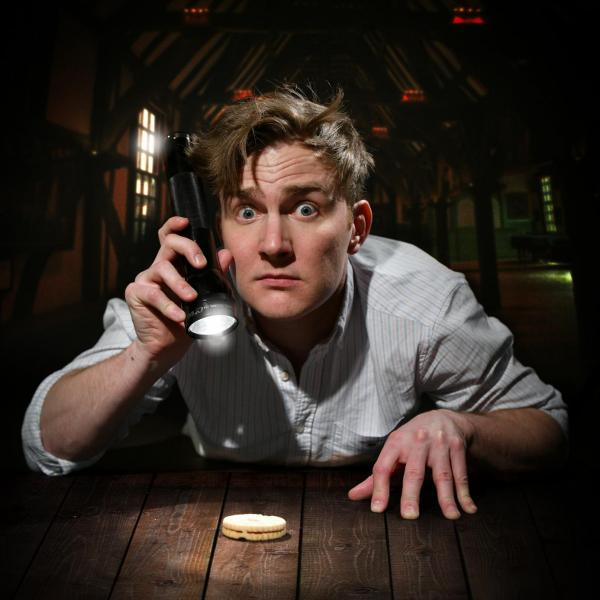 Tom Houghton looks up at the camera, confused while shining a flashlight on a biscuit