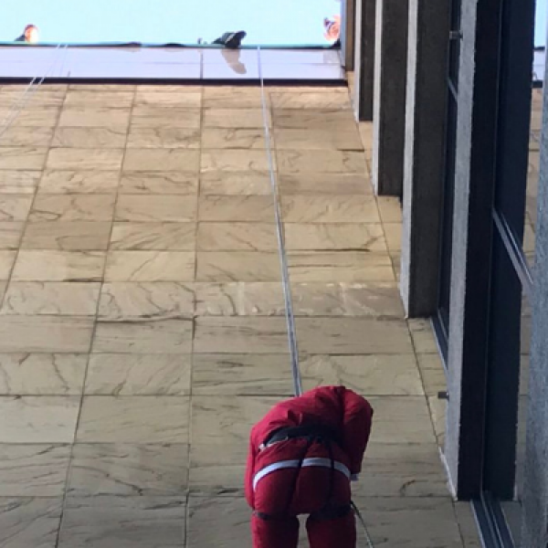 Two men wearing santa suits abseil down the building