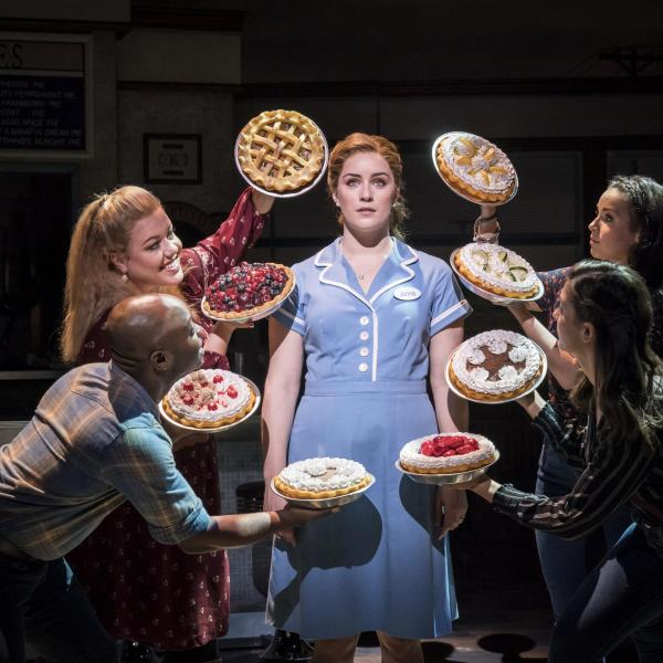 A waitress is singing, around her people are holding different pies.