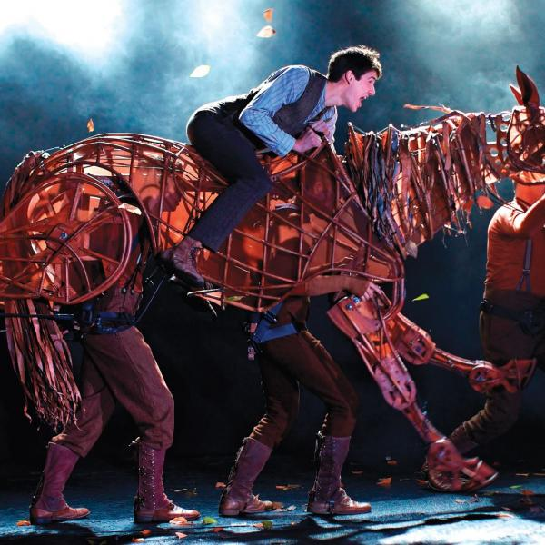 Still image shot on a theatre stage showing a young man riding a large life sized puppet of a horse