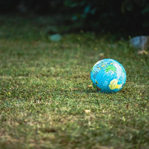 Blow up ball designed like the Earth resting on some grass