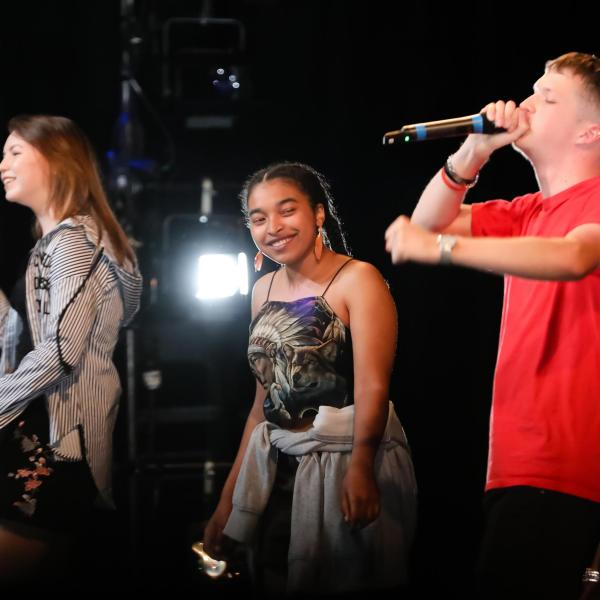 A diverse group of young people in a line on stage smiling, one holding a microphone